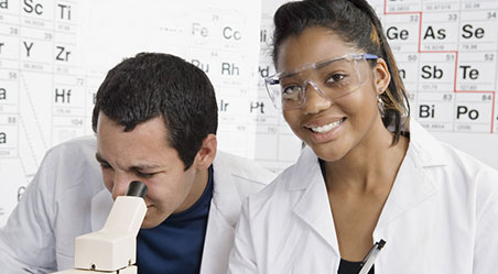 two students looking into a microscope with periodic table in background