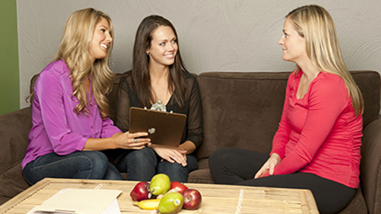 Three ladies sitting together on couches with fruit on a table in front of them discussing nutrition